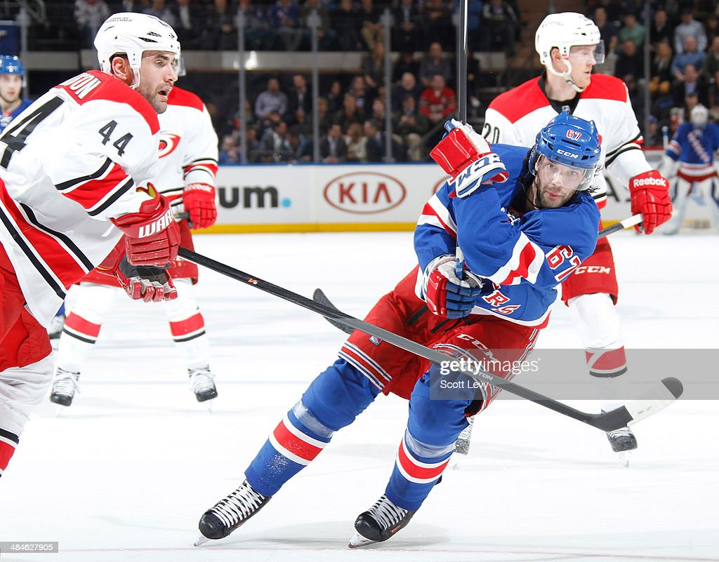 Benoit Pouliot of the New York Rangers skates for the puck against Jay Harrison and Riley Nash of the Carolina Hurricanes at Madison Square Garden on...