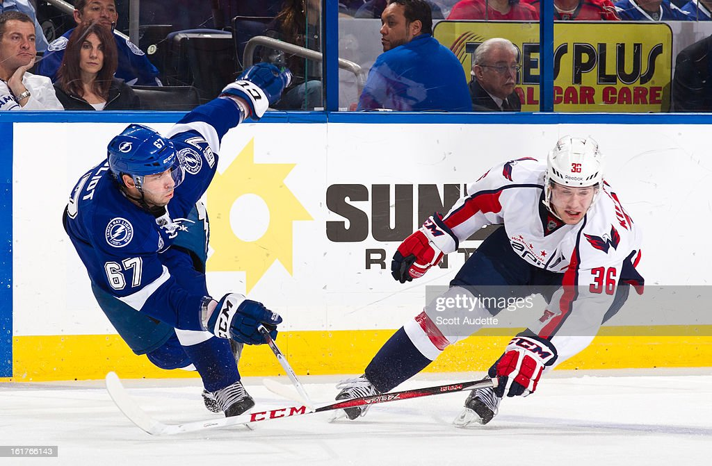 Benoit Pouliot #67 of the Tampa Bay Lightning and Tomas Kundratek #36 of the Washington Capitals both loose balance during a play during the second period of the game at the Tampa Bay Times Forum on February 14, 2013 in Tampa, Florida.
