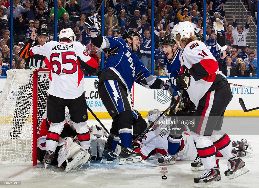 Benoit Pouliot #67 of the Tampa Bay Lightning celebrates a goal by teammate <a gi-track='captionPersonalityLinkClicked' href=/galleries/search?phrase=Matt+Carle&family=editorial&specificpeople=582495 ng-click='$event.stopPropagation()'>Matt Carle</a> #25 during the first period against the Ottawa Senators at the Tampa Bay Times Forum on January 25, 2013 in Tampa, Florida.