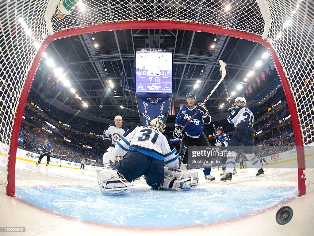 <a gi-track='captionPersonalityLinkClicked' href=/galleries/search?phrase=Benoit+Pouliot&family=editorial&specificpeople=879830 ng-click='$event.stopPropagation()'>Benoit Pouliot</a> #67 of the Tampa Bay Lightning looks at the puck as it crosses the goal line while <a gi-track='captionPersonalityLinkClicked' href=/galleries/search?phrase=Ondrej+Pavelec&family=editorial&specificpeople=3644118 ng-click='$event.stopPropagation()'>Ondrej Pavelec</a> #31 of the Winnipeg Jets neglects to make a save during the second period of the Tampa Bay Lightning game against the Winnipeg Jets at the Tampa Bay Times Forum on February 1, 2013 in Tampa, Florida.