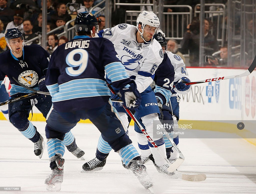 <a gi-track='captionPersonalityLinkClicked' href=/galleries/search?phrase=Benoit+Pouliot&family=editorial&specificpeople=879830 ng-click='$event.stopPropagation()'>Benoit Pouliot</a> #67 of the Tampa Bay Lightning watches the loose puck in front of <a gi-track='captionPersonalityLinkClicked' href=/galleries/search?phrase=Pascal+Dupuis&family=editorial&specificpeople=208971 ng-click='$event.stopPropagation()'>Pascal Dupuis</a> #9 of the Pittsburgh Penguins on February 24, 2013 at Consol Energy Center in Pittsburgh, Pennsylvania.