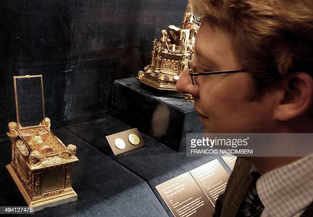 BenoitHenry Papounaud cocurator of the exhibition 'Sacres Royaux de Louis XIII a Charles X' looks at one of the principal objects in the coronation...