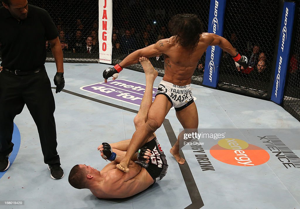 <a gi-track='captionPersonalityLinkClicked' href=/galleries/search?phrase=Benson+Henderson&family=editorial&specificpeople=8623964 ng-click='$event.stopPropagation()'>Benson Henderson</a> (white shorts) kicks <a gi-track='captionPersonalityLinkClicked' href=/galleries/search?phrase=Nate+Diaz&family=editorial&specificpeople=5532032 ng-click='$event.stopPropagation()'>Nate Diaz</a> (bottom) during their lightweight championship bout at the UFC on FOX event on December 8, 2012 at Key Arena in Seattle, Washington.