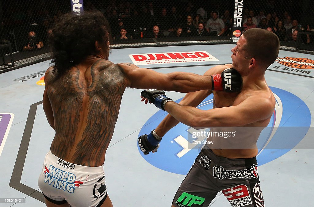Benson Henderson punches Nate Diaz during their lightweight championship bout at the UFC on FOX event on December 8, 2012 at Key Arena in Seattle, Washington.