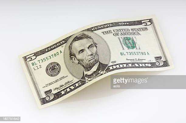 Bent five dollar bill