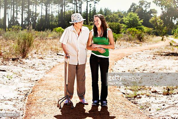 Bent old woman and young girl enjoy forest walk