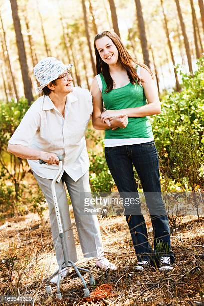 Bent old woman and young girl walk in forest