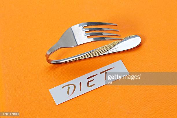 Bent silver fork as reminder of diet