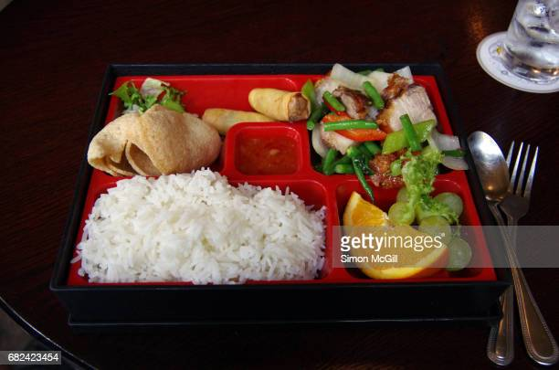Bento box with fried pork, green beans, rice, spring rolls, prawn crackers, an orange wedge and green grapes