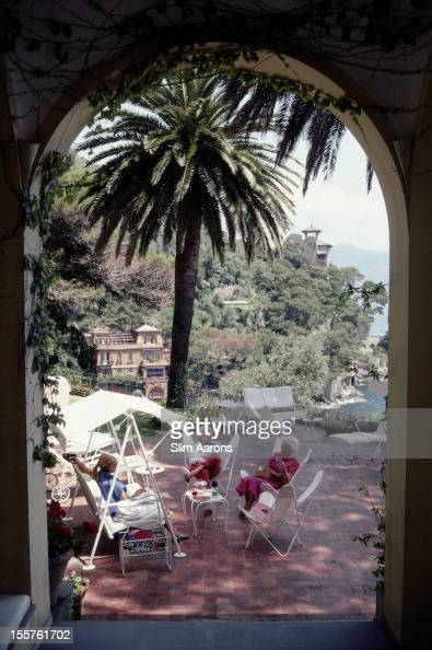 Beppe Croce and Umberta Croce relaxing in the shade of a palm tree on the terrace of their home in Portofino Italy in July 1985