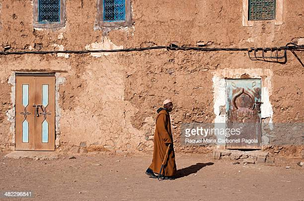 Berber man passing by an adobe house doorway in a small village