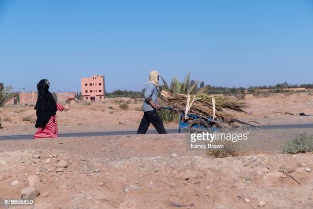 Berber Man  & Woman walking by Road near Marrakesh in Morocco with Cart.