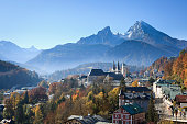 The city of Berchtesgaden in front of the Watzmann Mountains. European Alps, Germany. Trees colored by autumn.