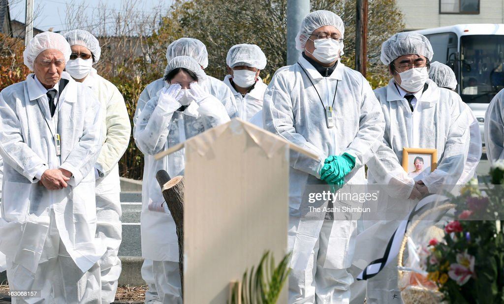 Bereaved families and former residents in radiation protective suits pray in front of the completed cenotaph located within the evacuation zone on March 2, 2013 in Futaba, Fukushima, Japan. The cenotaph was built at former town central, that is three kilometers from crippled Fukushima Daiichi Nuclear Power Plant. Japan is to commemorate second anniversary of the Great East Japan Earthquake and the following tsunami.