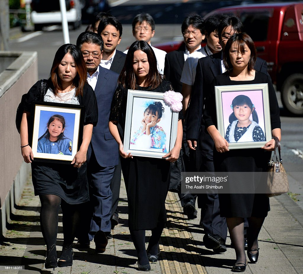 Bereaved families of children who died in tsunami caused by the Great East Japan Earthquake walk to the Sendai District Court on September 17, 2013 in Sendai, Miyagi, Japan. The court ordered a kindergarten in Ishinomaki and its principal to pay a total of 177 million yen (1.77 million U.S. dollars) in damages to the families. The court recognized the responsibility of the kindergarten for dispatching a bus to take children to their homes in the coastal area, despite the tsunami warning following the earthquake. The kindergarten, situated on a hill, did not suffer any damage from the tsunami.