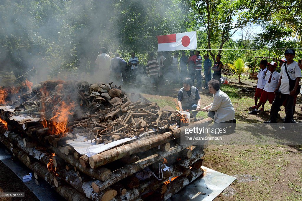 Bereaved family members add wood to a fire during a ceremony to cremate the remains of Japanese troops on Biak island on November 25, 2013 in Biak, Indonesia. Japanfs Ministry of Health, Labor and Welfare sent a delegation to the island in Papua province after the remains of 282 people were recently uncovered. During the war, the Imperial Japanese Army designated Biak island as Japan's 'absolute zone of national defense.' In the battles against allied forces, an estimated 10,000 or more people were killed on the island.