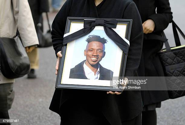 A bereaved family members of Ghanaian deportee Abubakar Awudu Sraj enters the Tokyo District Court with his portrait on March 19 2014 in Tokyo Japan...