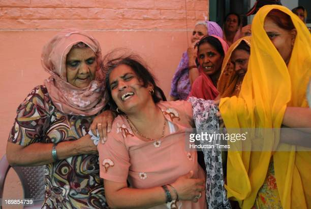 Bereaved family members of Preeti Rathi who died of injuries following an acid attack in Mumbai at her home in Narela village on June 3 2013 in New...