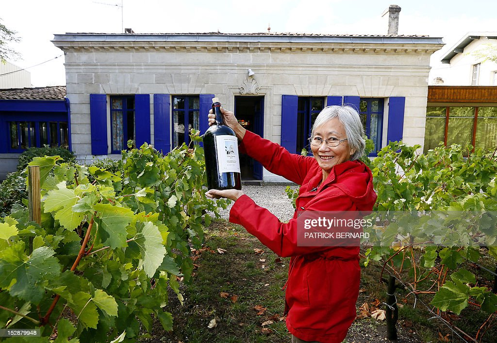 FRAYSSE - Berenice Chang Ricard poses with a bottle of wine she prepared a previous year after harvesting grapes with relatives in the garden of her house, on September 27, 2012 in Bordeaux, southwestern France.