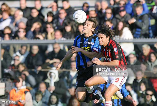 AC Milan's forward Filippo Inzaghi heads the ball with Atalanta's defender Gianpaolo Bellini during their Italian serie A football match at Bergamo's...