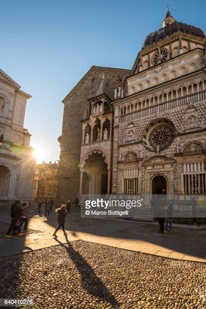 Bergamo, Italy. Tourists walking in front of St Mary Major (Santa Maria Maggiore) Basilica at sunrise.