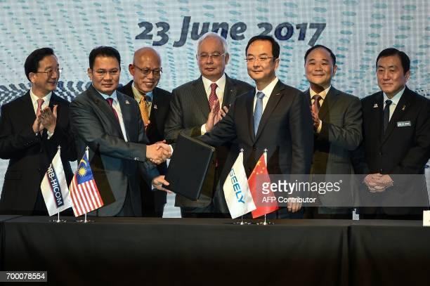 Berhad's Syed Faisal Albar and President of the Zhejiang Geely Holding Group and CEO of Geely Auto Group An Conghui shake hands and exchange...