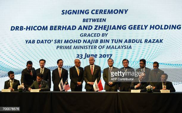 Berhad's Syed Faisal Albar and President of the Zhejiang Geely Holding Group and CEO of Geely Auto Group An Conghui sign documents as Malaysia's...