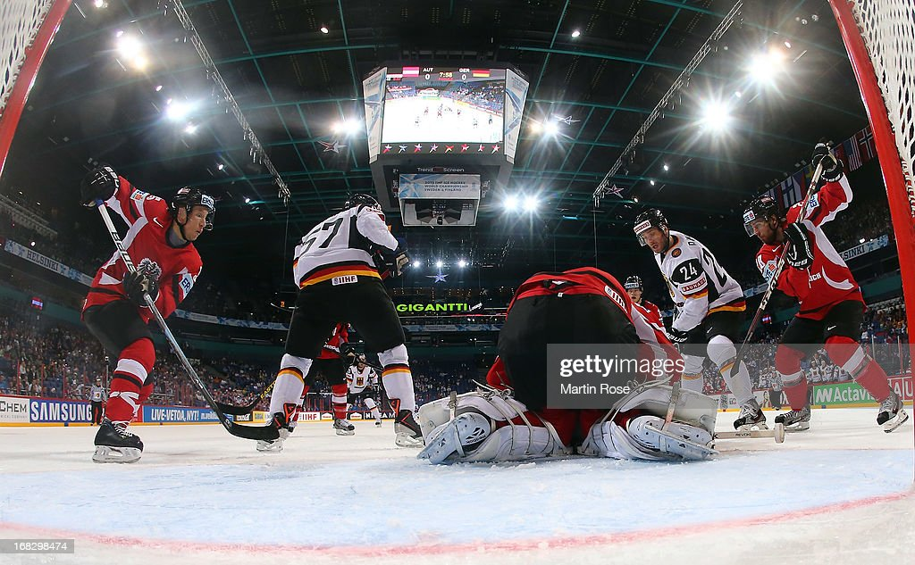 Berhard Starkbaum (C), goaltender of Austria makes a save on <a gi-track='captionPersonalityLinkClicked' href=/galleries/search?phrase=Andre+Rankel&family=editorial&specificpeople=684400 ng-click='$event.stopPropagation()'>Andre Rankel</a> (#24) of Germany during the IIHF World Championship group H match between Austria and Germany at Hartwall Areena on May 8, 2013 in Helsinki, Finland.