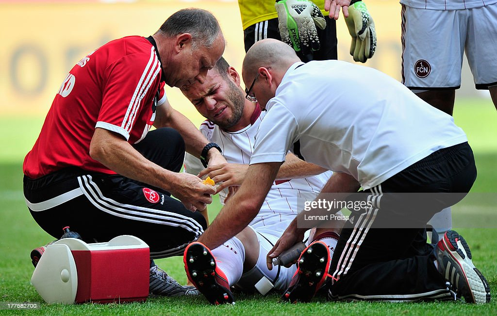 Berkay Dabanli (C) of Nuernberg recieves medical treatment during the Bundesliga match between FC Bayern Muenchen and 1. FC Nuernberg at Allianz Arena on August 24, 2013 in Munich, Germany.