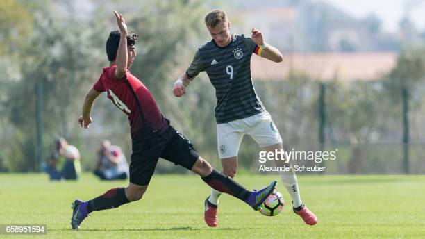 Berkehan Bicer of Turkey challenges JannFiete Arp of Germany during the UEFA U17 elite round match between Germany and Turkey on March 28 2017 in...