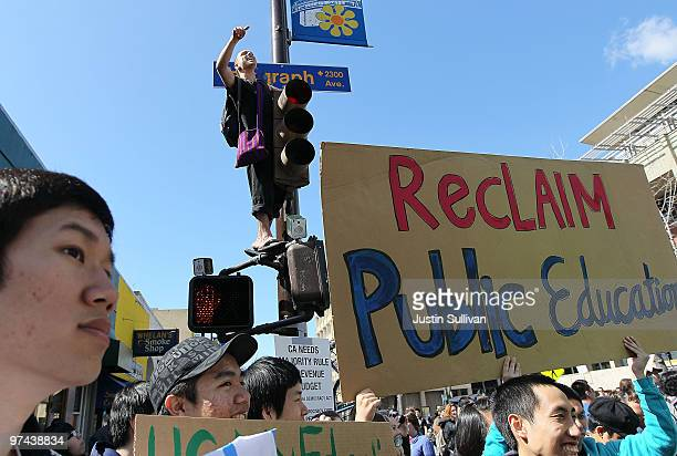 Berkeley student climbs on a street light as protestors carry signs during a march through campus during a national day of action against funding...