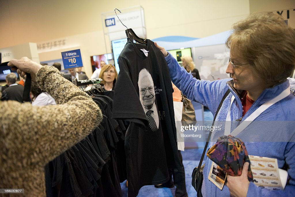Berkshire Hathaway Inc. shareholders look over merchandise on the exhibition floor during the Berkshire shareholders meeting in Omaha, Nebraska, U.S., on Saturday, May 4, 2013. Warren Buffett's Berkshire Hathaway Inc.'s cash hoard hit a record as first-quarter profit jumped 51 percent on gains from equity-linked derivatives and insurance operations. Photographer: Daniel Acker/Bloomberg via Getty Images