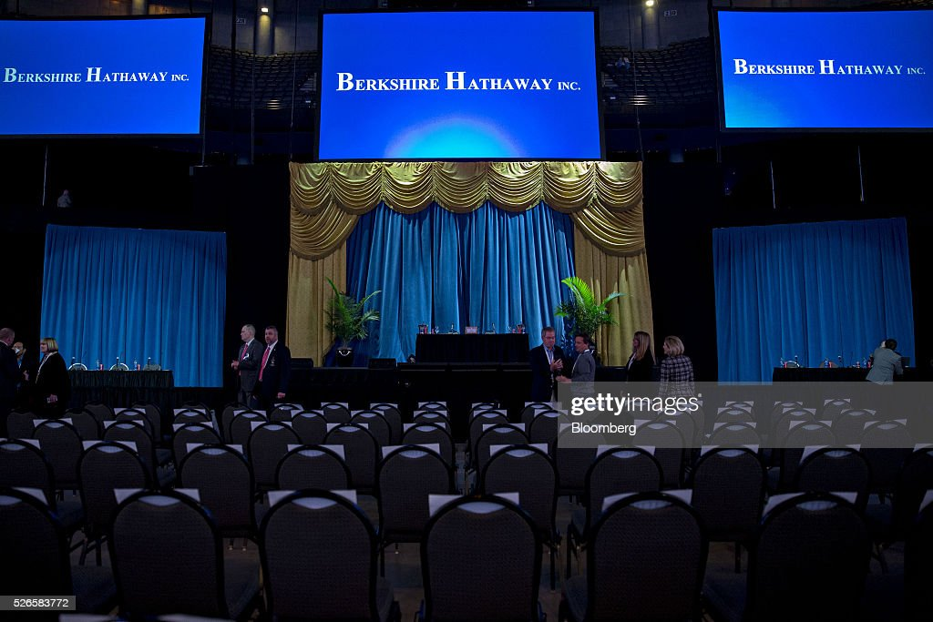 Berkshire Hathaway Inc. signage appears on screens above the stage ahead of the company's annual shareholders meeting in Omaha, Nebraska, U.S., on Saturday, April 30, 2016. Dozens of Berkshire Hathaway Inc. subsidiaries will be showing off their products as Chief Executive Officer Warren Buffett hosts the company's annual meeting. Photographer: Daniel Acker/Bloomberg via Getty Images