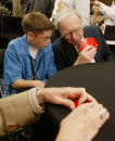 Berkshire Hathaway's CEO Warren Buffett helps Stephen Comp of Irvine CA with a hand of Bridge before a news conference May 4 2003 in Omaha Nebraska...