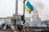 Berkut riot police hang a Ukrainian flag from a street light on Independence Square on February 19 2014 in Kiev Ukraine After several weeks of calm...