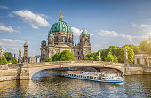 Beautiful view of historic Berlin Cathedral (Berliner Dom) at famous Museum Island with ship passing Friedrichsbrucke bridge on Spree river in golden evening light at sunset in summer, Berlin, Germany