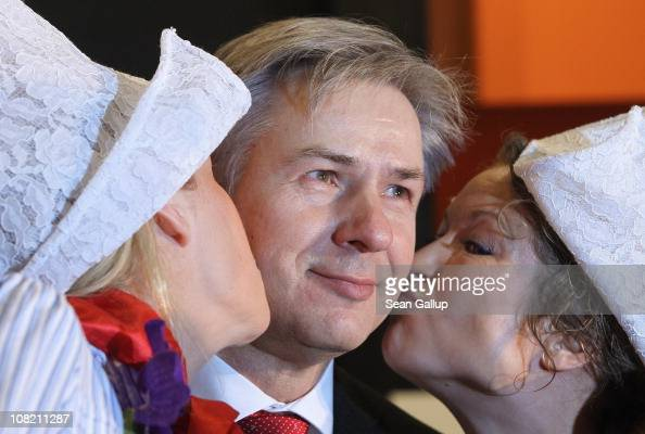 Berlin city mayor Klaus Wowereit gets a kiss at a Dutch foods and agricultural stand while touring the 2011 Gruene Woche international agricultural...