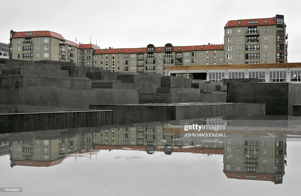 A prefabricated cement building ubiquitous in the former east Berlin is reflected in the wet surface of a stelle at the Memorial for the Murdered...