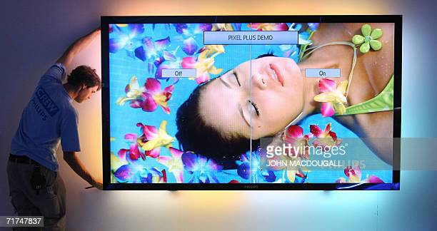 A technician installs a 100inch LCD TV with ambilight at Dutch electronics giant Philips' stand at Berlin's IFA Consumer Electronics trade fair 30...