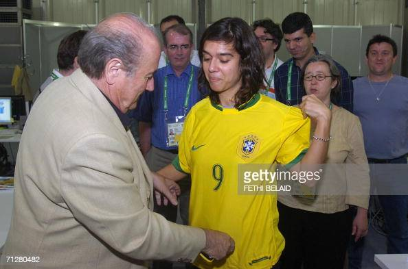 FIFA President Sepp Blatter offers to Marina Passos an AFP journalist from Brazil a jersey of the Brazilian national football team wearing number 9...