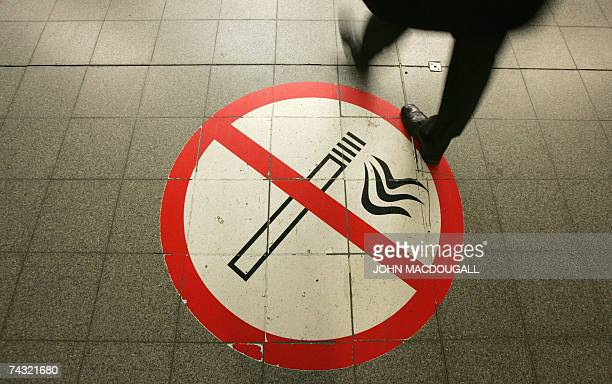 FILES Picture taken 26 February 2007 shows a passenger walking on a nosmoking sign at the Potsdamer Platz train station in Berlin The German...