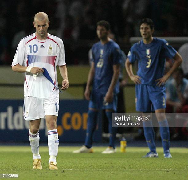French midfielder Zinedine Zidane removes the captain's armband as he leaves the pitch after receiving a red card as Italian defender Fabio Grosso...