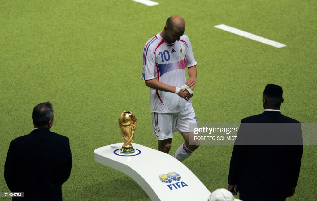 French midfielder Zinedine Zidane (C) walks past the World Cup trophy being guarded by security as he leaves the pitch after getting a red card for head-butting Italian defender Marco Materazzi during the World Cup 2006 final football match between Italy and France at Berlin's Olympic Stadium, 09 July 2006. Italy won 5-4 in a penalty shootout after the teams finished in extra time 1-1.