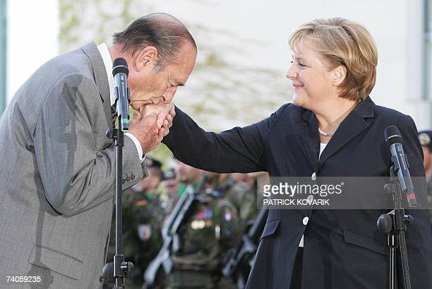 French President Jacques Chirac kisses German Chancellor Angela Merkel's hand after giving a statement at the Chancellory 03 May 2007 in Berlin as he...