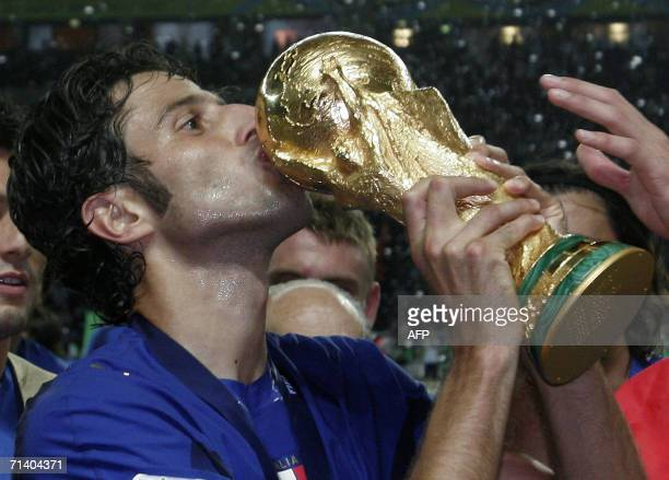 Italian defender Fabio Grosso kisses the 2006 World Cup trophy after Italy won their final football match against France at Berlins Olympic Stadium...