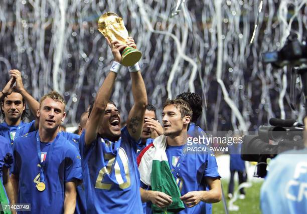 Italian midfielder Daniele De Rossi Italian midfielder Simone Perrotta and Italian midfielder Francesco Totti celebrate with the trophy after the...