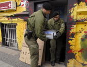 Policemen carry computer equipment confiscated during a raid 09 May 2007 in Berlin's Kreuzberg district German police staged raids against militant...