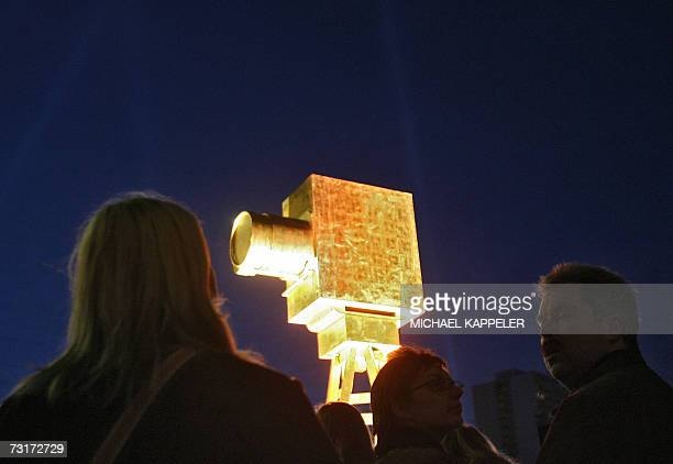 Spectators walk past a giant mockup of the 'Goldene Kamera' award standing besides the red carpet in front of the Axel Springer publishing house 01...