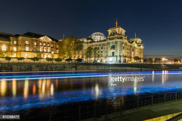 Berlin - in the government district at blue hour with light trails of a sightseeing boat