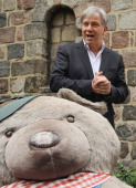 Berlin Mayor Klaus Wowereit has a look at giant teddy bears in the Nikolaiviertel district while on a walking tour with senior citizens on August 17...